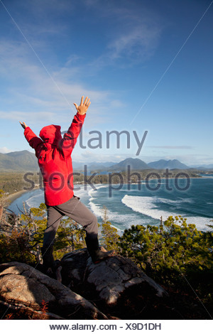A Man Wearing A Red Jacket Looks Out At The View Of Cox Bay Near Tofino With Arms Raised; British Columbia, Canada - Stock Photo