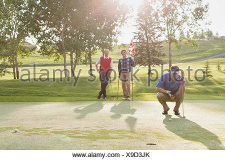 golfer focussed on putt while friends watch - Stock Photo