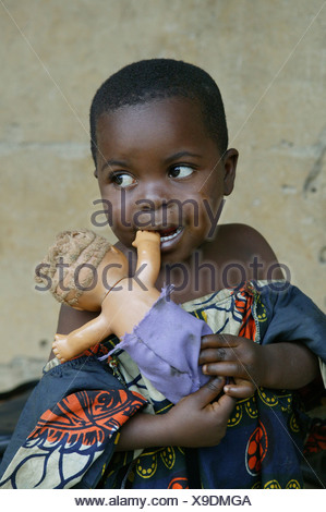 Young African girl holding a white doll, Cameroon, Africa - Stock Photo