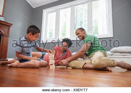 Family on the floor playing a game at home. - Stock Photo