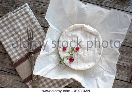 Camembert cheese on piece of paper, decorated with redcurrants and thyme. - Stock Photo