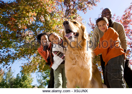 Family walking golden retriever in autumn park smiling low angle view portrait - Stock Photo