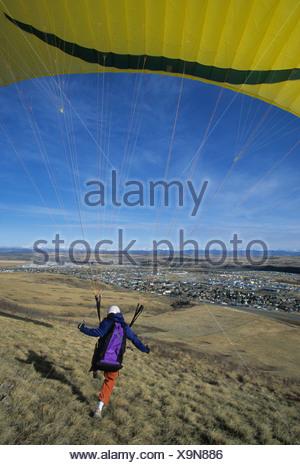 A paraglider landing on a grassy field in Cochrane, Alberta, Canada - Stock Photo