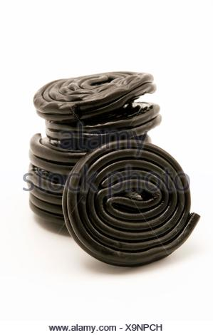 Black liquorice wheels on a white background - Stock Photo