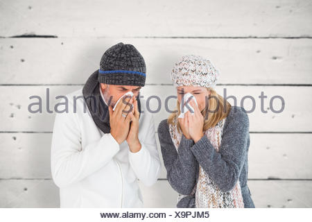 Composite image of sick couple in winter fashion sneezing - Stock Photo
