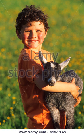 boy carrying a young goat on his arms - Stock Photo