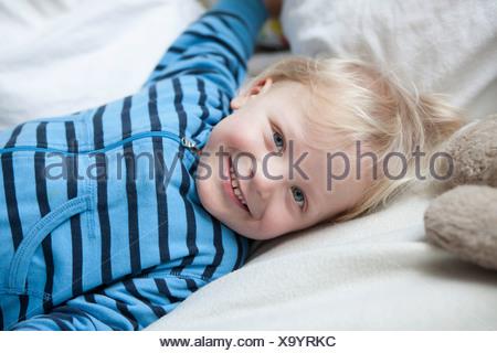 Portrait of smiling little boy lying on blanket - Stock Photo