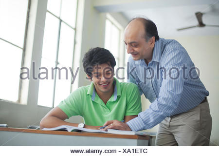 Professor holding beakers with chemicals - Stock Photo