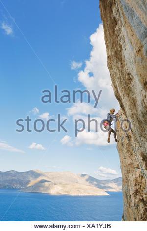 Greece, Dodecanese, Kalymnos, Rock climber on steep cliff - Stock Photo