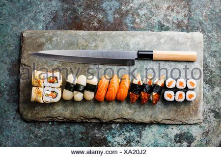 Sushi rolls and nigiri with Japanese knife on stone slate background - Stock Photo