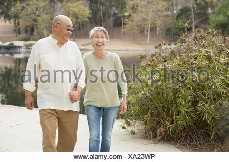 Senior couple walking along pathway, holding hands, laughing - Stock Photo