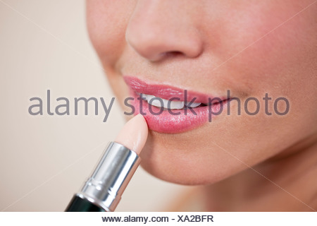 A young woman applying lipstick, close up - Stock Photo