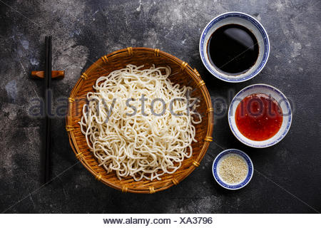 Raw Udon noodles in bamboo basket with sauces and sesame on dark background - Stock Photo