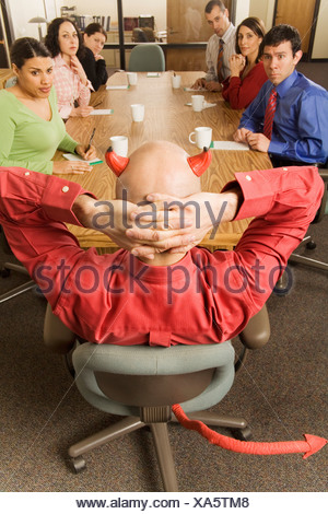 Businessman with devil horns and tail at meeting - Stock Photo