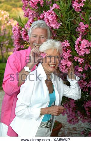happy senior citizen couple in the garden of their summer residence - Stock Photo