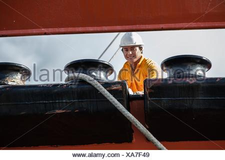 Worker fastening ropes to mooring posts on oil tanker - Stock Photo