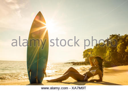 Woman lying on the beach with a surfboard, Bali, Indonesia - Stock Photo