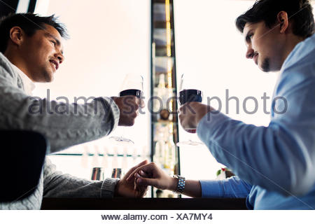 Low angle view of gay couple toasting red wine glasses at bar counter - Stock Photo