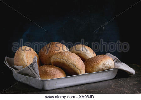 Fresh baked wholegrain buns on gray kitchen towel in vintage aluminum tray over dark table with black background. - Stock Photo