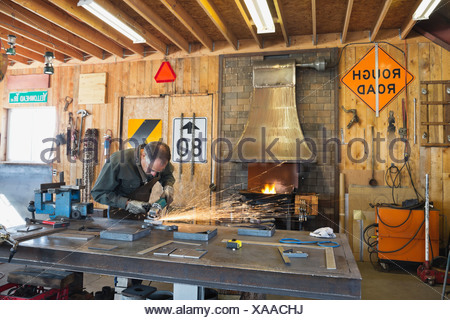 Worker grinding metal at workbench - Stock Photo