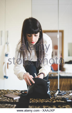 Young woman looking in makeup bag in bedroom - Stock Photo