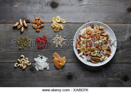 White ceramic bowl full with a healthy trail mix of dried fruits, nuts and seeds. Shot areal view with ingredients seporated and - Stock Photo
