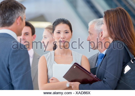 Portrait of confident businesswoman among co-workers - Stock Photo
