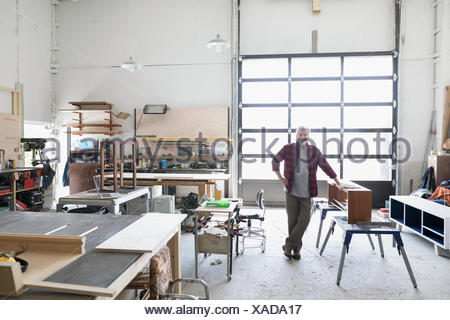 Portrait confident male carpenter leaning on wood bench in workshop - Stock Photo