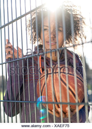 Portrait of young woman with basketball standing behind a fence - Stock Photo