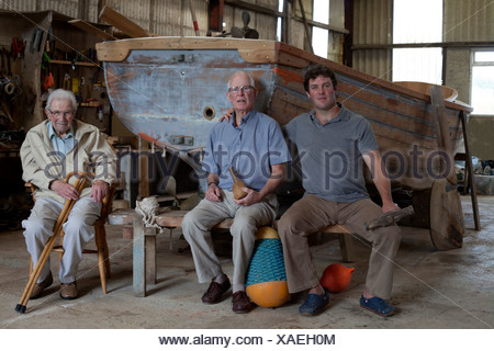 Group portrait of three generations of male boat builders - Stock Photo