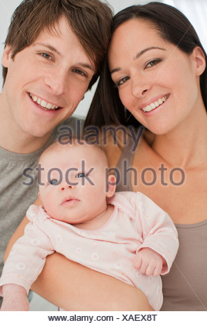 Close up of smiling parents holding baby - Stock Photo