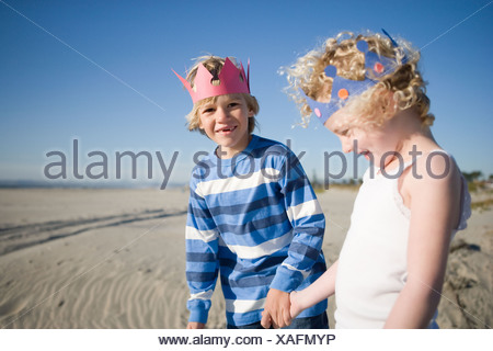 Brother and sister wearing paper crowns holding hands - Stock Photo