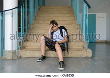 A worried pre-adolescent boy sitting on stairs in a school - Stock Photo
