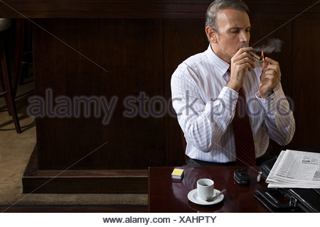 Businessman smoking cigar - Stock Photo