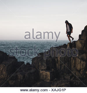Man Standing On Cliff By Sea Against Sky - Stock Photo