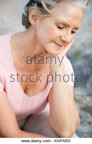 Portrait of a senior woman at the beach looking sad - Stock Photo