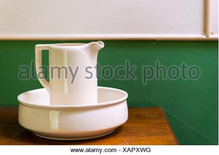 Tilburg, Netherlands. Ewer, watercan and bowl placed on a dressoir against a green and white interior wall. - Stock Photo
