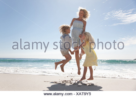 Family playing on beach - Stock Photo