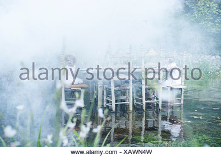 Children sitting at dining table floating on pond, surrounded by smoke - Stock Photo
