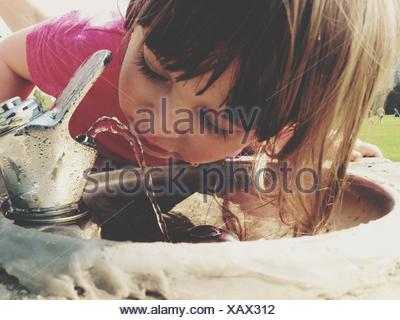 Close-Up Of Girl Drinking Water From Faucet Outdoors - Stock Photo
