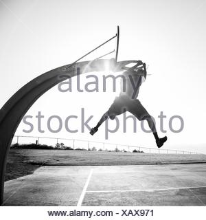 Young man shooting hoops in a park, Los Angeles, California, USA - Stock Photo