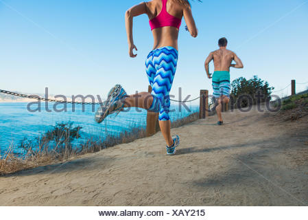 Mid adult man and young woman running on path by sea, rear view - Stock Photo