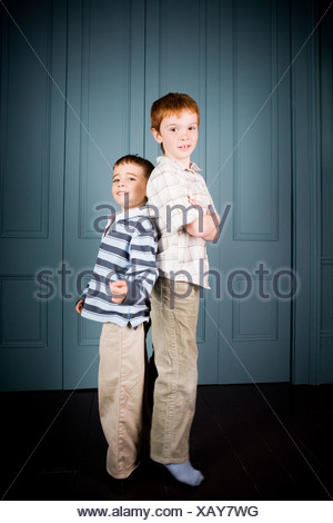 Older and younger boy standing back to back - Stock Photo
