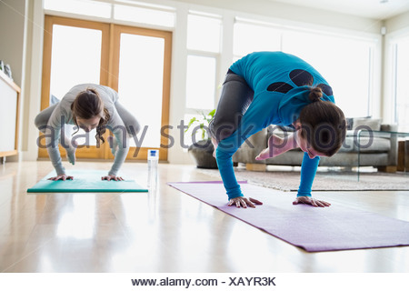 Mother and daughter doing yoga in living room - Stock Photo