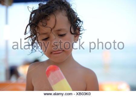 Girl eating an ice-cream on the beach, Thassos, Greece - Stock Photo