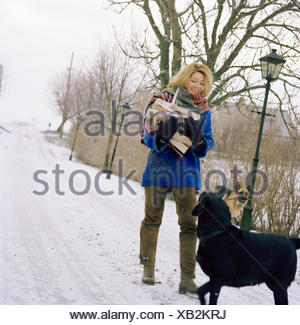Scandinavian woman with dogs in the snow, Sweden. - Stock Photo