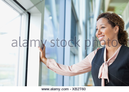 Smiling businesswoman looking out window in office - Stock Photo