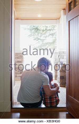 father and son sitting in doorway - Stock Photo