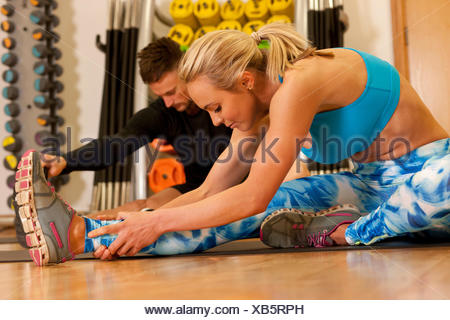 Man and woman in gym sitting on floor doing leg stretching exercises - Stock Photo