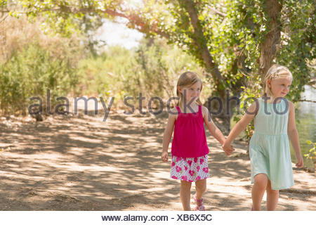 Two young sisters strolling and holding hands on riverbank - Stock Photo